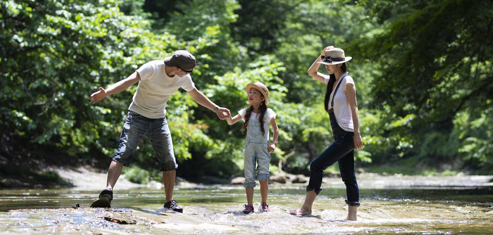 Family of 3 playing in a stream - Protect the Ones You Love with Accidental Death Insurance plus Dismemberment