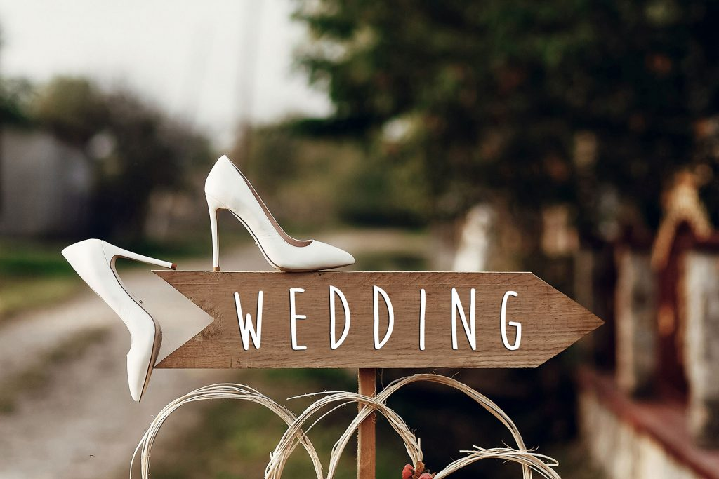 Crafty wood wedding sign with white Bridal shoes guiding guests to a wedding event.