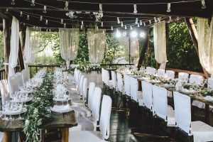 Wedding reception event with white decor under a wooden pavilion.