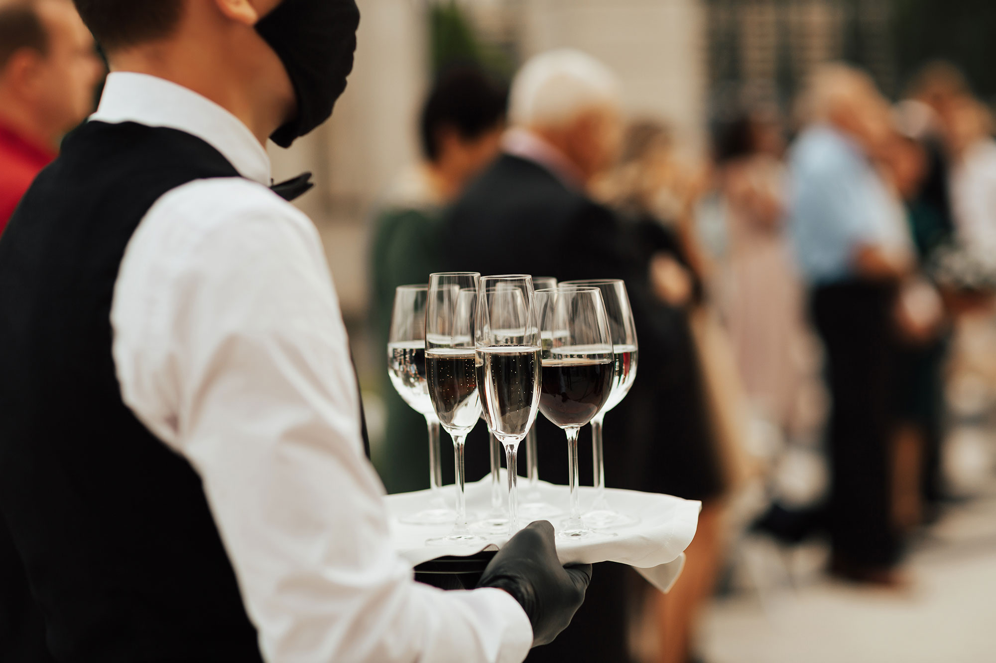 Waiter with wine glasses wearing PPE - Outdoor party - event insurance protection